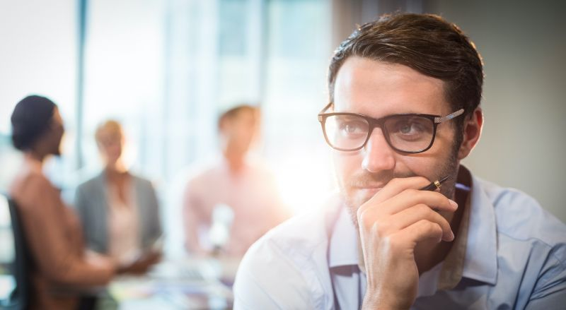 Thoughtful man with hand on chin while coworker interacting in the background in the office